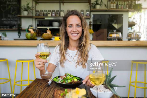 portrait of smiling woman holding glass of wine in a cafe - food and drink fotografías e imágenes de stock