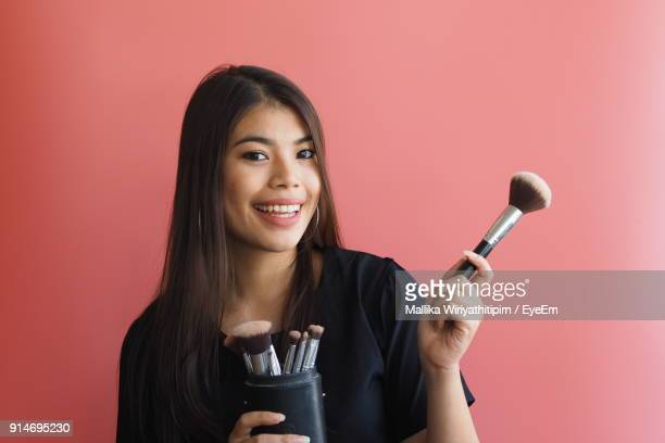 Portrait Of Smiling Woman Holding Make-Up Brush Against Colored Background