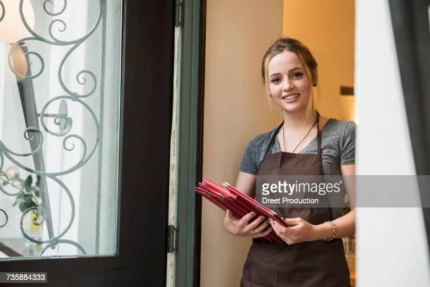 Portrait of smiling woman holding menu