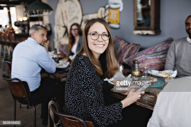 portrait of smiling woman holding mobile phone while sitting with friends at table - kleine personengruppe stock-fotos und bilder