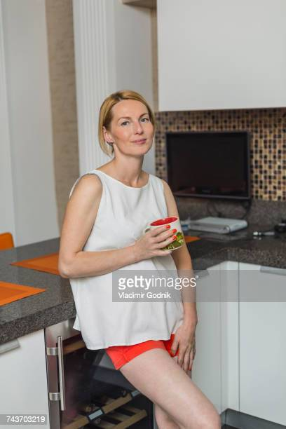 Portrait of smiling woman holding mug while leaning at counter in kitchen