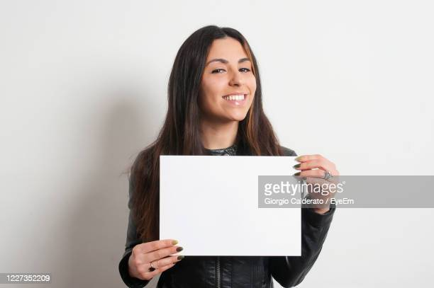 portrait of smiling woman holding paper against white background - placard stock pictures, royalty-free photos & images