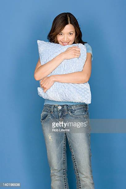 Portrait of smiling woman holding pillow on blue background, studio shot