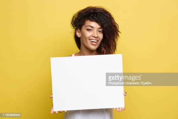 portrait of smiling woman holding placard while standing on yellow background - person holding up sign stock pictures, royalty-free photos & images