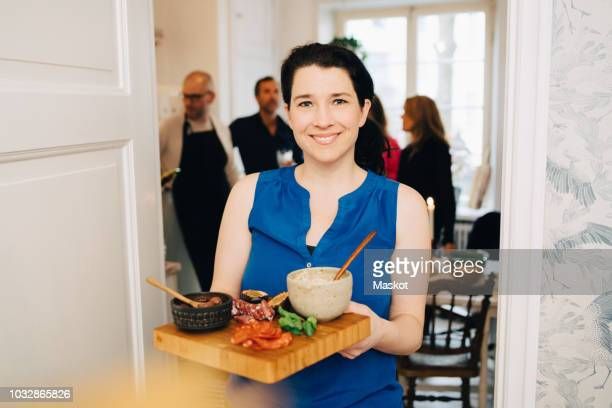 Portrait of smiling woman holding serving tray while standing at doorway in party