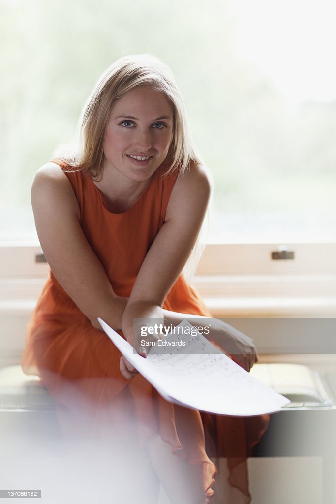 Portrait of smiling woman holding sheet music near window : Stock Photo
