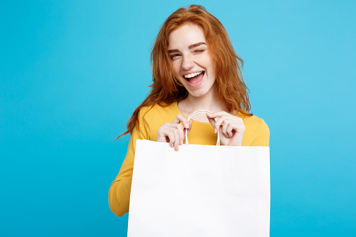 Portrait Of Smiling Woman Holding Shopping Bag Against Blue Background - gettyimageskorea