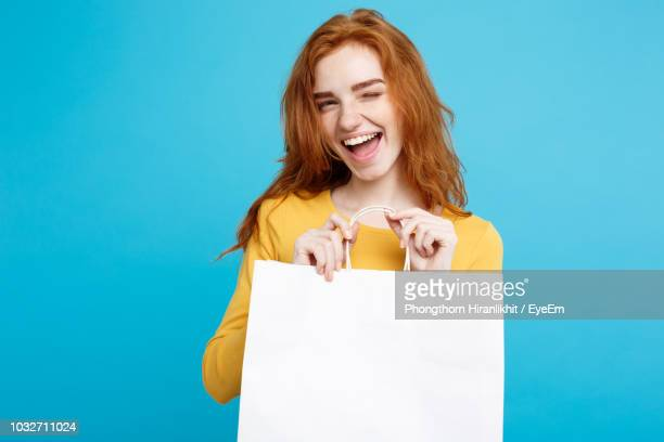 portrait of smiling woman holding shopping bag against blue background - バッグ ストックフォトと画像