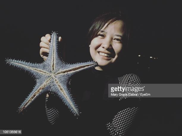 portrait of smiling woman holding starfish at night - mary moody fotografías e imágenes de stock
