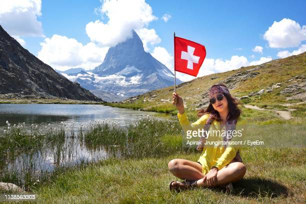 portrait of smiling woman holding swiss flag while sitting on grassy field by lake - drapeau suisse photos et images de collection