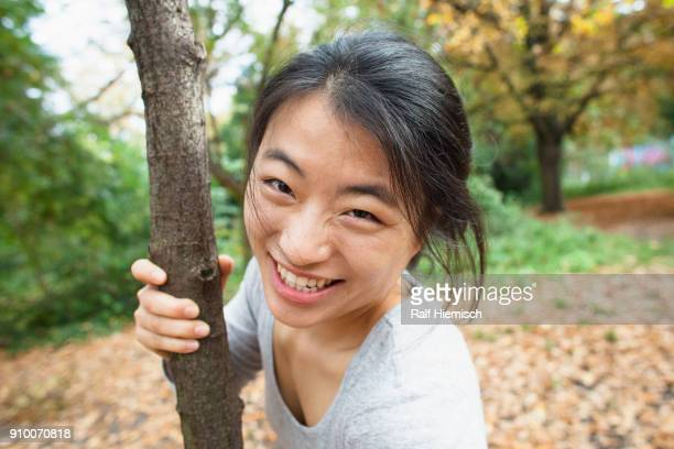 Portrait of smiling woman holding tree trunk while standing at park