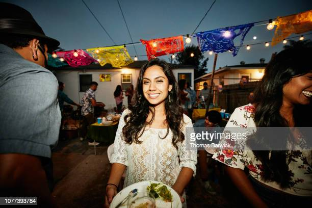 Portrait of smiling woman in backyard during party with friends on summer evening