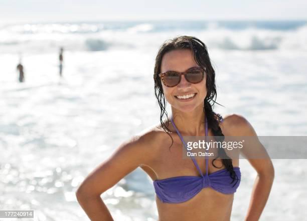 Portrait de femme souriante en bikini et lunettes de soleil à la plage