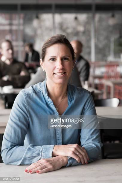 portrait of smiling woman in cafe - personne secondaire photos et images de collection