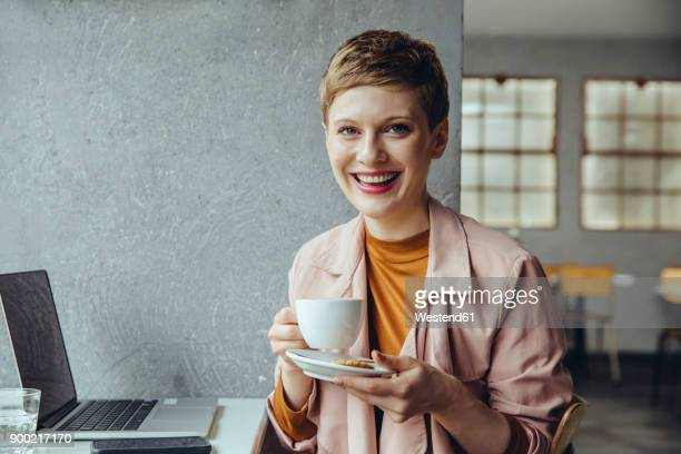 Portrait of smiling woman in cafe with laptop and cup of coffee