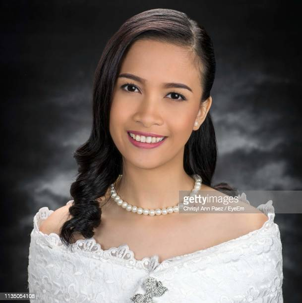 portrait of smiling woman in dress and necklace against wall - pearl necklace stock pictures, royalty-free photos & images