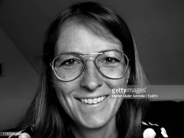 Portrait Of Smiling Woman In Eyeglasses At Home