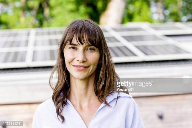 portrait of smiling woman in front of a house with solar panels on the roof - solar equipment stock pictures, royalty-free photos & images
