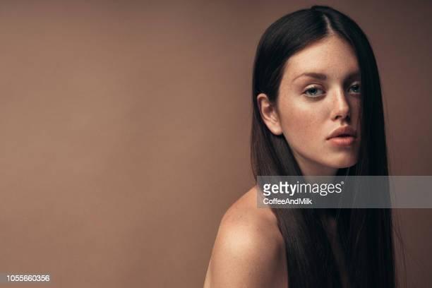 portrait of smiling woman in front of black wall - beleza natural imagens e fotografias de stock