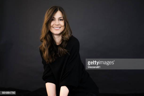 portrait of smiling woman in front of black wall - brown hair stock pictures, royalty-free photos & images