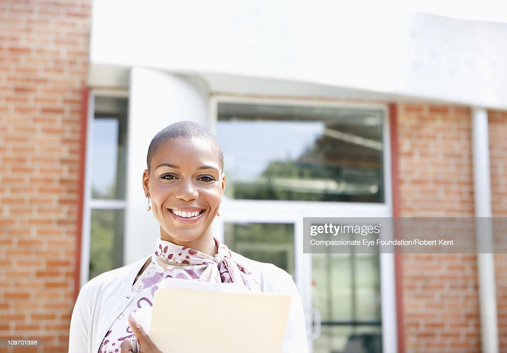Portrait of smiling woman in front of building : Stock Photo