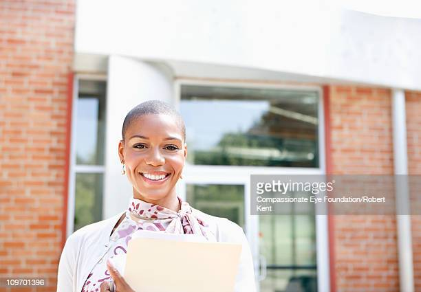 """portrait of smiling woman in front of building - """"compassionate eye"""" stock pictures, royalty-free photos & images"""