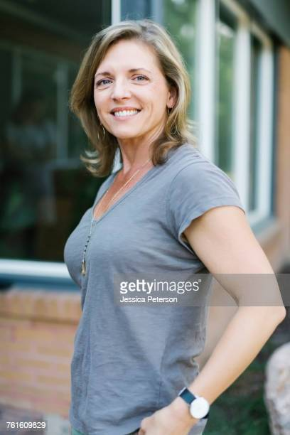 portrait of smiling woman in front of house - short sleeved stock pictures, royalty-free photos & images