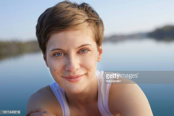 portrait of smiling woman in front of lake - one mid adult woman only stock pictures, royalty-free photos & images