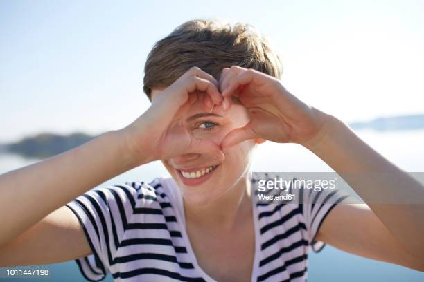 portrait of smiling woman in front of lake shaping heart with her fingers - women in see through tops stock photos and pictures