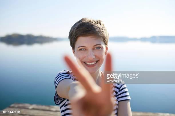 portrait of smiling woman in front of lake showing victory sign - friedenszeichen handzeichen stock-fotos und bilder