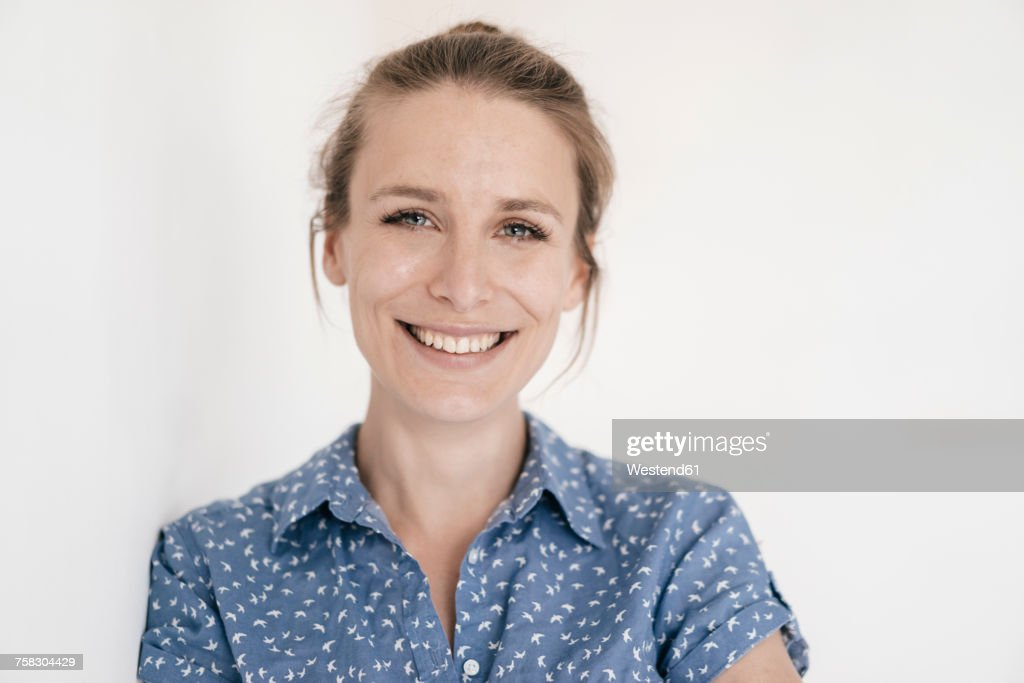 Portrait of smiling woman in front of white background : Stock Photo
