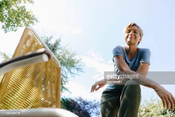 portrait of smiling woman in garden next to chair - inquadratura dal basso foto e immagini stock