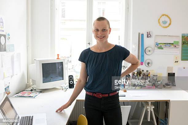 portrait of smiling woman in home office - shaved head stock pictures, royalty-free photos & images