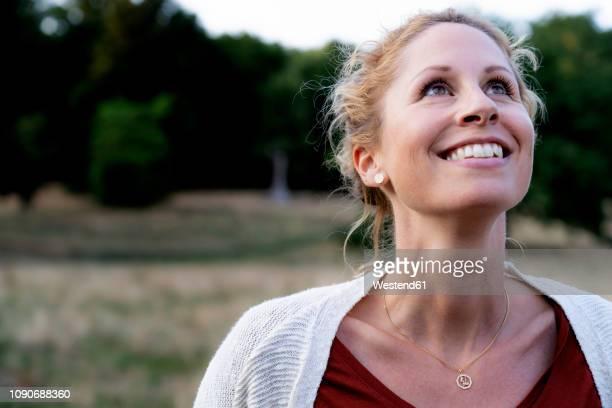 portrait of smiling woman in nature looking up - blick nach oben stock-fotos und bilder