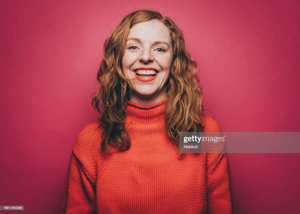 Portrait of smiling woman in orange top against pink background : Stock Photo