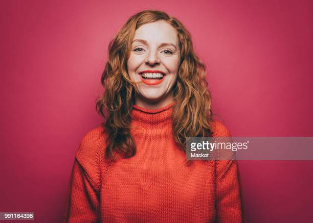 portrait of smiling woman in orange top against pink background - lächeln stock-fotos und bilder