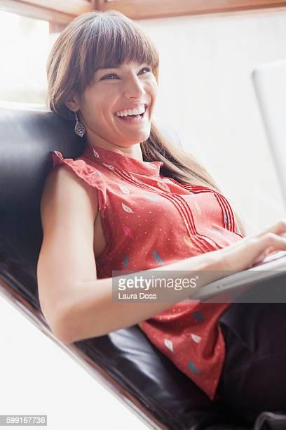 portrait of smiling woman in recliner using laptop - laura belli foto e immagini stock