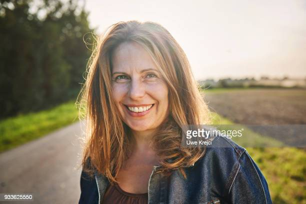 portrait of smiling woman in the countryside - older woman stock pictures, royalty-free photos & images