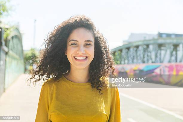 Portrait of smiling woman in urban area.