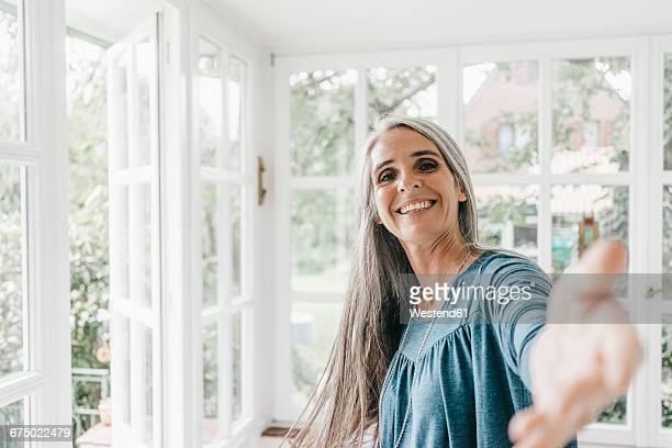 Portrait of smiling woman inviting viewer in her winter garden