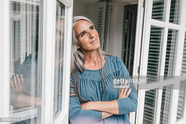 Portrait of smiling woman leaning against door case of her winter garden