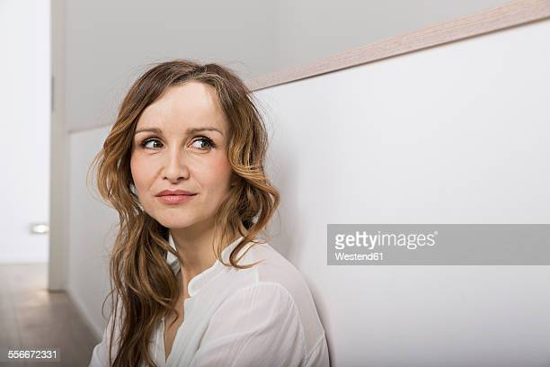 Portrait of smiling woman leaning against wall