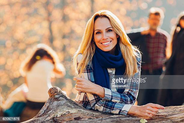 Portrait of smiling woman leaning on a trunk