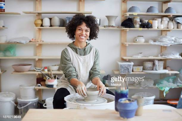 portrait of smiling woman learning pottery in art studio - pottery stock pictures, royalty-free photos & images