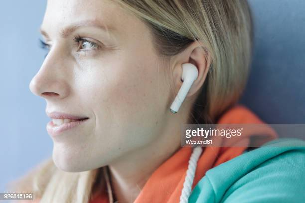 portrait of smiling woman listening music with wireless earphones, close-up - bluetooth stock pictures, royalty-free photos & images