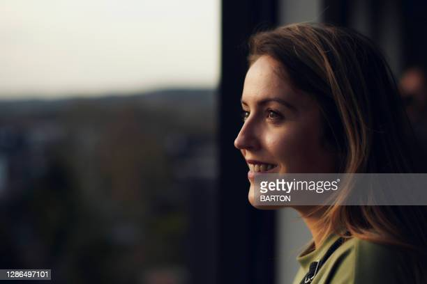 portrait of smiling woman looking out of window - greater london stock pictures, royalty-free photos & images