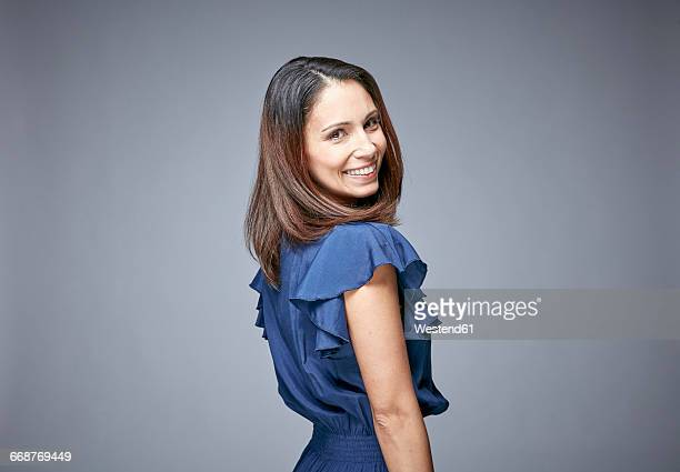 portrait of smiling woman looking over her shoulder - blue dress stock pictures, royalty-free photos & images