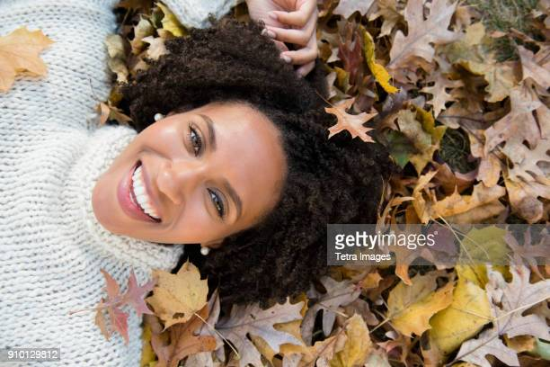 portrait of smiling woman lying down on autumn leaves in park - mid adult woman sweater stock pictures, royalty-free photos & images