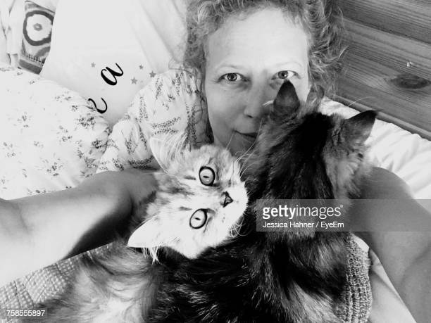 Portrait Of Smiling Woman Lying On Bed With Cats At Home