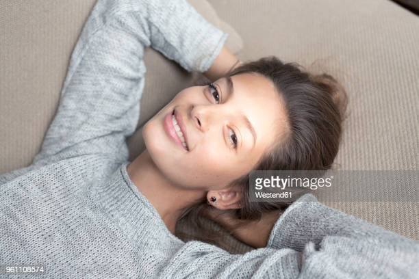 portrait of smiling woman lying on couch - hygge stock pictures, royalty-free photos & images